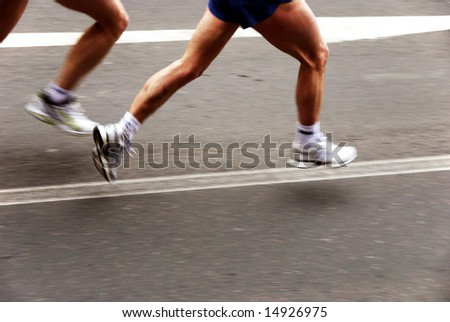 detail of the legs of two marathon runners with slight panning effect - stock photo