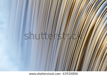 Detail of the Little Pigeon River cascade illuminated with reflected color from sunlit autumn trees, Pigeon Forge, Tennessee, USA - stock photo