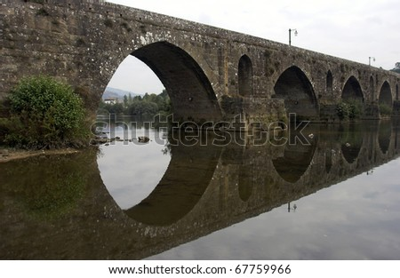 Detail of the old bridge of Ponte de Lima (north of Portugal) with reflection - stock photo