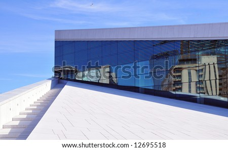 Detail of the opera house in Oslo Norway, with reflections of the city of Oslo in the glass - stock photo