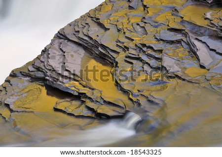 Detail of the Presque Isle River during autumn, illuminated by reflected golden color from sunlit foliage, Michigan's Upper Peninsula, USA - stock photo