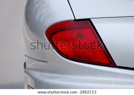 Detail of the rear end of a silver car with focus on the brake lights. - stock photo