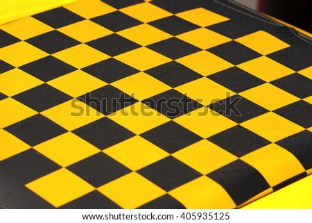 Detail of the roof of a car, yellow and black checkered. Fabric sunroof