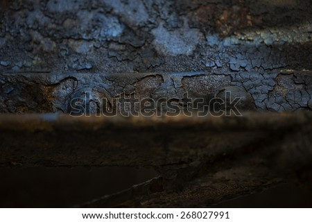 Detail of the weathered and rusting underside of a steel railroad bridge. Image shows peeling paint and rusted steel beams and rivets.  - stock photo