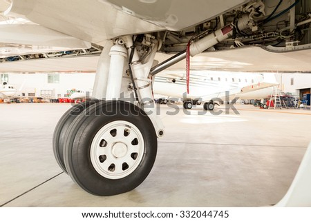 Detail of the wheel and landing gear on a small corporate passenger jet parked inside a hangar at an airport with a view of a second aircraft visible behind
