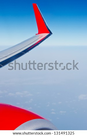 Detail of the wing of plane over the clouds in front of a blue sky - stock photo