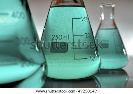 detail of three flasks containing green liquid - stock photo