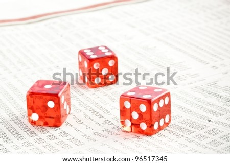 detail of three red dice on the financial newspaper - stock photo