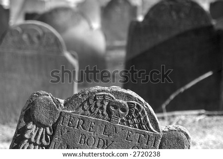 detail of top of tomb stone with others out of focus in the background, detail shows skull with wings - stock photo