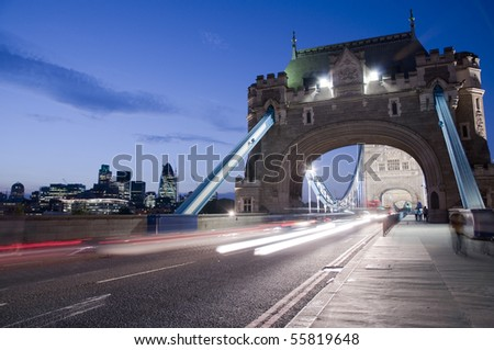 Detail of Tower Bridge in London at dusk with car light trail and city in the background. - stock photo
