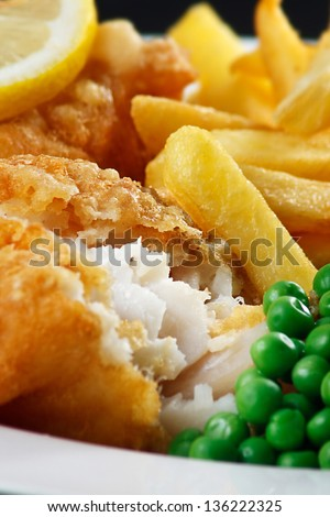 detail of traditional fish and chips with peas and a slice of lemon. - stock photo