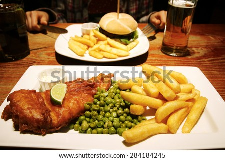 detail of traditional fish and chips with peas and a slice of lemon and dip