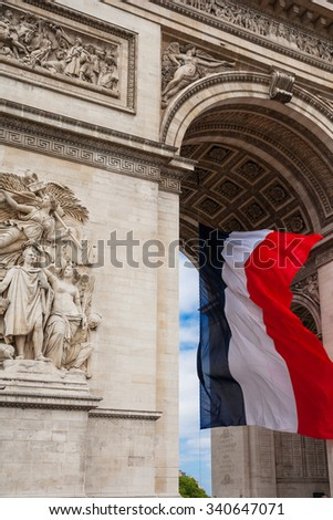 Detail of Triumphal Arch (Arc de Triumphe) wiith national flag of France, Paris - stock photo