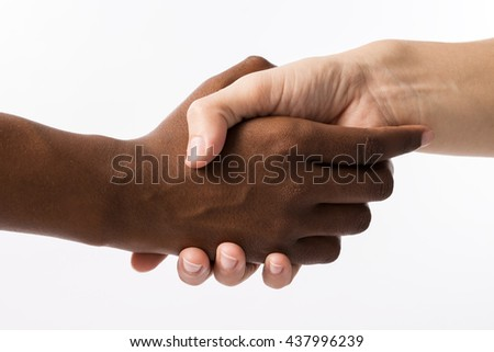 Detail of two people giving hands. There is a white hand and a black hand, isolated in a white background. This image suggests equality between races. - stock photo