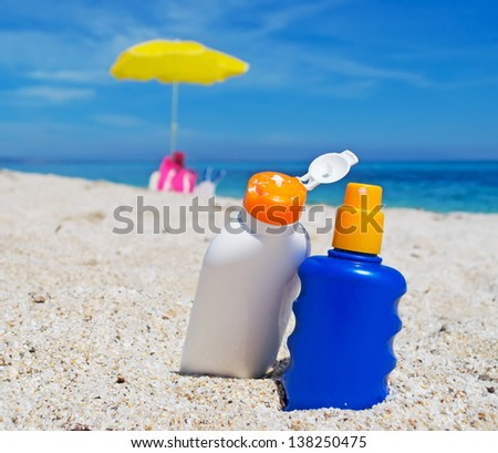 detail of two suntan lotion bottles on the sand - stock photo