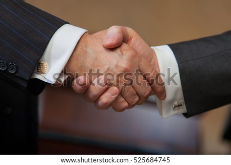 Detail of two well-dressed businessman shaking hands. Handshake image.