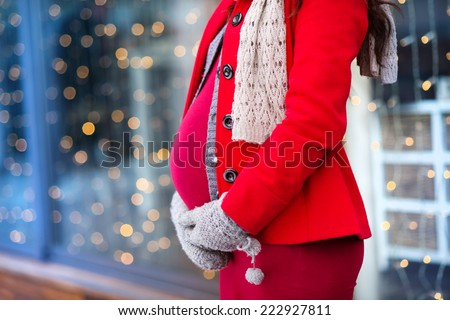 Detail of unrecognizable pregnant woman's belly in winter outside the shops - stock photo