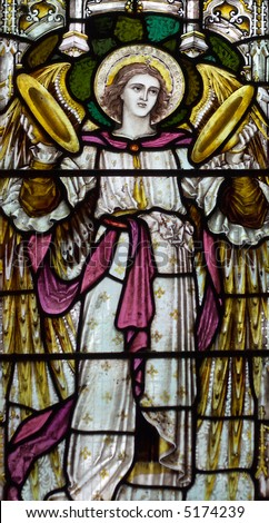 detail of victorian stained glass church window in Fringford depicting a typical victorian angel with cymbals in his hands - stock photo