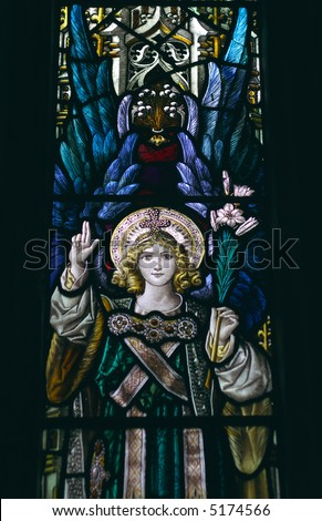 detail of victorian stained glass church window in Fringford depicting a typical victorian angel with a lily in his hands - stock photo