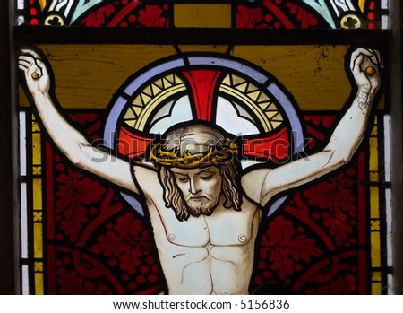 detail of victorian stained glass church window in Fringford depicting Jesus nailed to the cross - stock photo