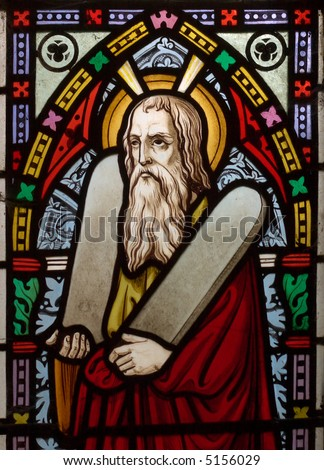 detail of victorian stained glass church window in Fringford depicting Moses with the tablets of covenant in his arms, interestingly without text, means he is pictured before climbing Mount Sinai - stock photo