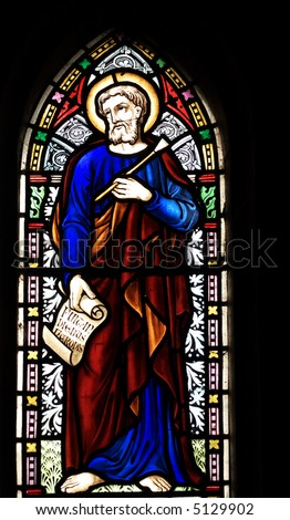 "detail of victorian stained glass church window in Fringford depicting St Luke the Evangelist, a scroll in his hands with the beginning of his gospel in latin ""Fuit in diebus herodes"" - stock photo"