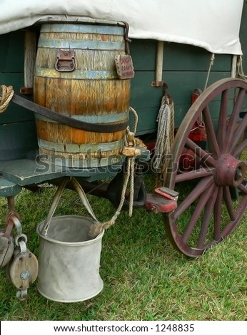 Detail of vintage American prairie wagon sitting on green grass. Vertical image shows a water barrel with a canvas bucket on the side of a green wagon with a big red wagon wheel with other details - stock photo