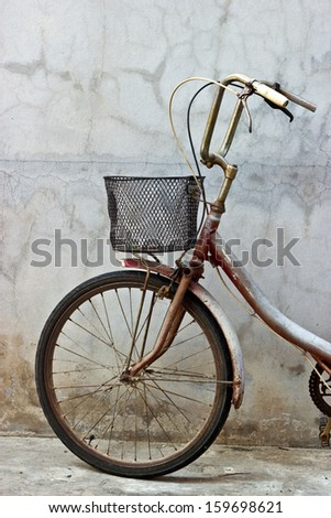 Detail of vintage bicycle leaning against a wall - stock photo