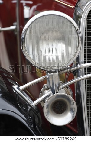 Detail of vintage car. Close-up of headlight and horn at classic car show - stock photo