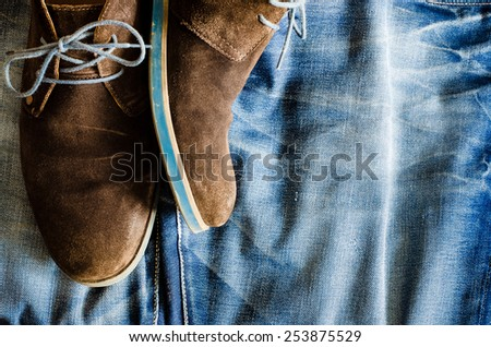 Detail of vintage leather shoes lying on denim fabric - stock photo
