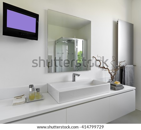 detail of washbasin in a modern bathroom with television and large mirror - stock photo