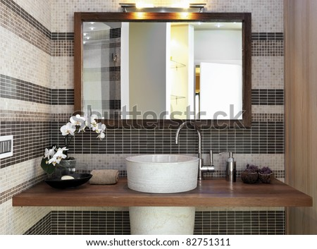 detail of washbasin in modern bathroom with a vase of white orchid - stock photo