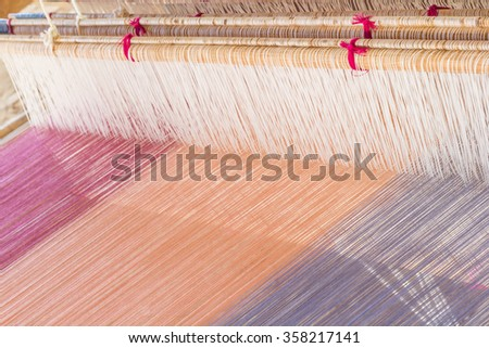 Detail of weaving loom for homemade silk or textile production - stock photo