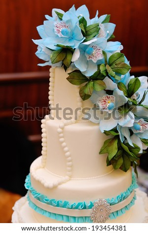 Detail of wedding cake with blue flowers - stock photo