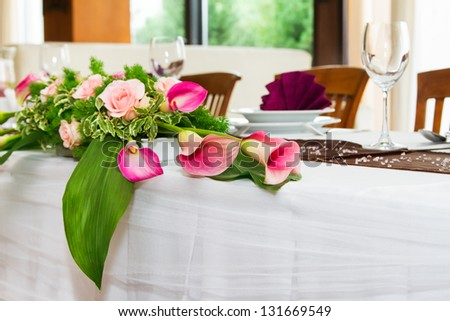 Detail of wedding table set with pink kalas and peach roses - stock photo