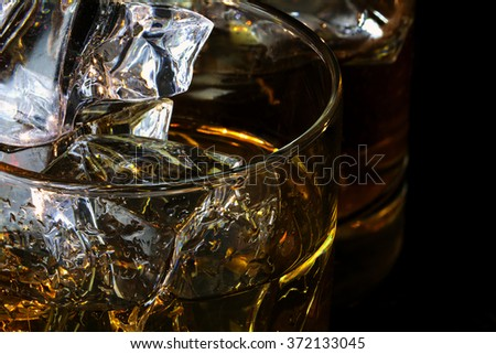 detail of whiskey glasses with ice cubes against a dark background, close up with selected focus and narrow depth of field - stock photo