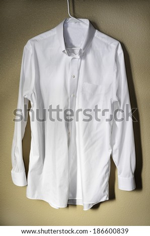 Detail of white dress shirt hanging on hanger with light - stock photo