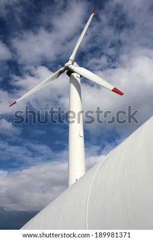 detail of wind mill power turbine under cloudy sky - stock photo