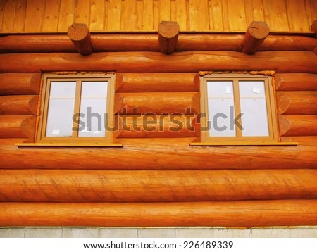 Detail of window built in wooden beams cabin wall. Painted wood with fungicide light red paint.  - stock photo