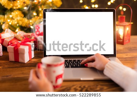 Detail of woman hand working on laptop with empty screen on wooden table. Blur Christmas tree and gifts on background