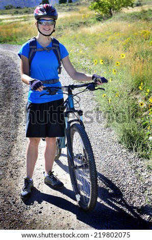 Detail of woman mountain biking wearing blue exercise shirt and helmet - stock photo