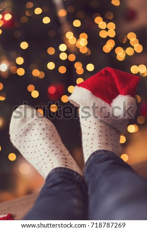 Detail of woman's feet wearing warm winter socks and small Santa's hat, placed on the table with nicely decorated Christmas tree and Christmas lights in the background. Selective focus