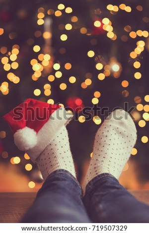 Detail of woman's feet wearing warm winter socks and small Santa's hat, placed on the table with Christmas tree and Christmas lights in background. Selective focus