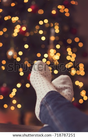 Detail of woman's feet wearing warm winter socks, placed on the table with nicely decorated Christmas tree and Christmas lights in the background. Selective focus
