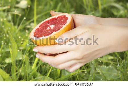 Detail of woman's hands holding a half of grapefruit over grass