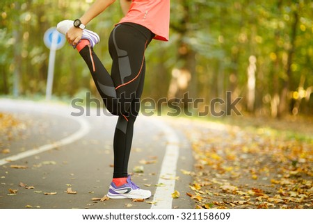 Detail of woman stretching legs before jogging in autumn nature - stock photo