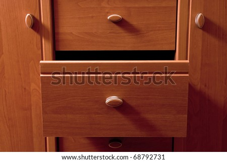 Detail of wooden chest of drawers. With shadows - stock photo