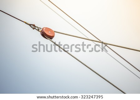 Detail of wooden rigging pulley and ropes on sail ship - stock photo