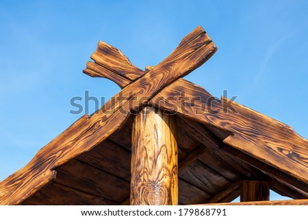 Detail of wooden roof gable over blue sky