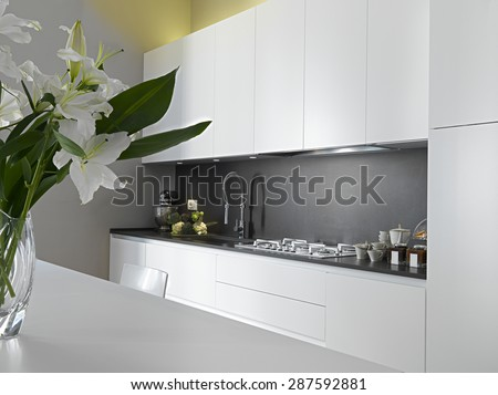 detail of worktop in a modern kitchen and vase of flowers on the table - stock photo
